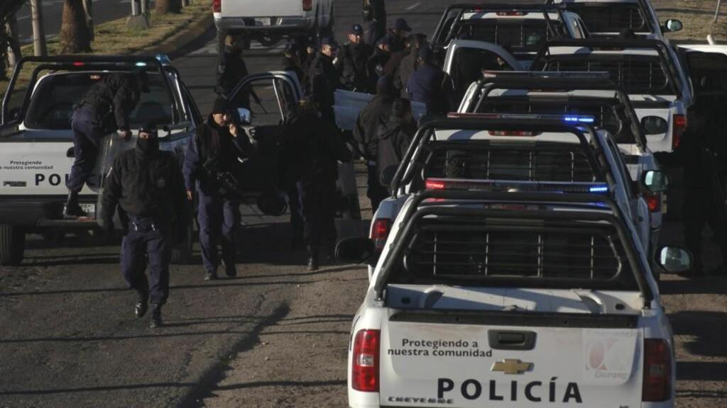 VOKTER DØDSVEIEN: Flere politimenn er på vakt langs veier i Durango hvor det har vært flere drap den siste tiden. Dette bildet ble tatt 20. januar, etter at det brøt ut kamper mellom innsatte i et fengsel i Durango. 35 døde i dette angrepet. FOTO: EPA/Fermín Soto Muñoz / Newspaper Victoria de Dur