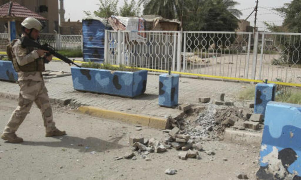 KRATER:  En av bombene i Bagdad i formiddag lagde dette hullet i fortauet. FOTO: REUTERS/SCANPIX.