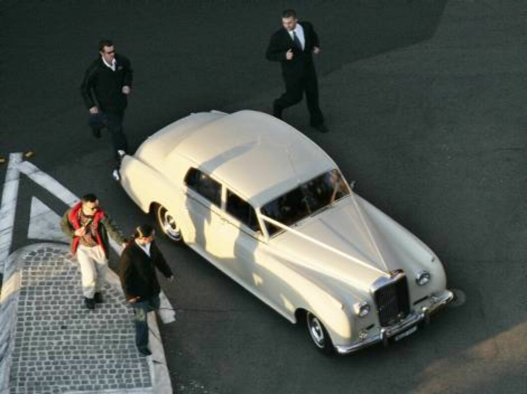Security staff run beside the bridal car of Oscar winning actress Nicole Kidman as she leaves her waterfront home to marry country music star Keith Urban, in Sydney, Sunday, June 25, 2006. Around 230 guests were expected to watch the pair exchange vows at Foto: AP/Scanpix