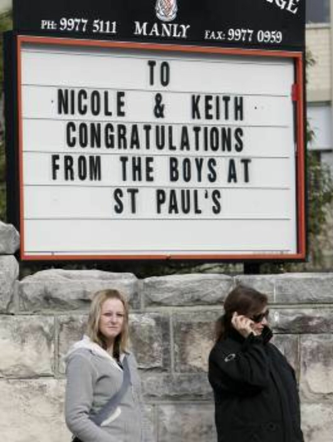 Two women wait near a sign at the chapel where Oscar-winning actor Nicole Kidman  is set to marry country music star Keith Urban, Sydney Sunday, June 25, 2006. Several thousand people lined the street for chance to glimpse Kidman and Urban. (AP Photo/Rick Foto: AP/Scanpix