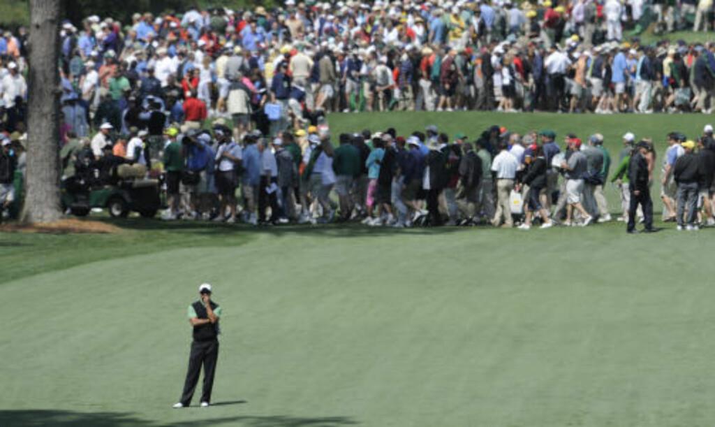 STILLE FØR STORMEN: Tiger Woods betrakter det sjuende hullet på runden mens tilskuerne stimler seg rundt golffenomenet. Foto: AFP PHOTO /TIMOTHY A. CLARY