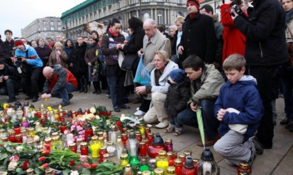 MINNES DE DØDE: Sørgende polakker samlet seg utenfor presidentpalasset i Warsawa etter at det ble kjent at presidentflyet med 96 personer om bord hadde styrtet. Foto: EPA/Tomasz Gzell/Scanpix