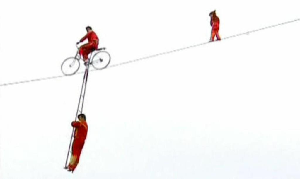 DRISTIG: Den akrobatiske truppen driver halsbrekkende stunts ni meter over tigerinnhegningen. Lille Xiaoyan (3) går bakerst. Foto: Reuters