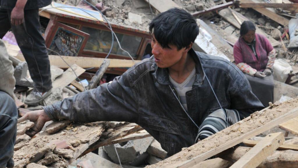 LETER I RUINENE: Redningsarbeidere og lokalbefolkningen leter etter jordskjelvofre. Redningsarbeidet er vanskelig fordi det rammede området i Qinghai-provinsen i Kina ligger i stor høyde, over 4 000 meter over havet. Foto: AFP PHOTO/SCANPIX