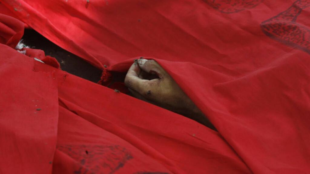BLODIG BANGKOK:  Et rødt banner dekker liket til en drept demonstrant. Foto: REUTERS/Kerek Wongsa