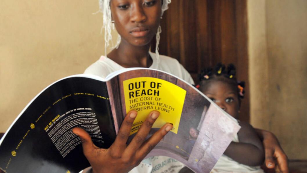 <strong>MORLØS:</strong> Lille Maya fra Sierra Leone mistet moren sin under fødselen. Her sitter hun i tantes armkrok som leser en rapport fra Amnesty om mødredødelighet i det vest-afrikanske landet. Foto: AFP