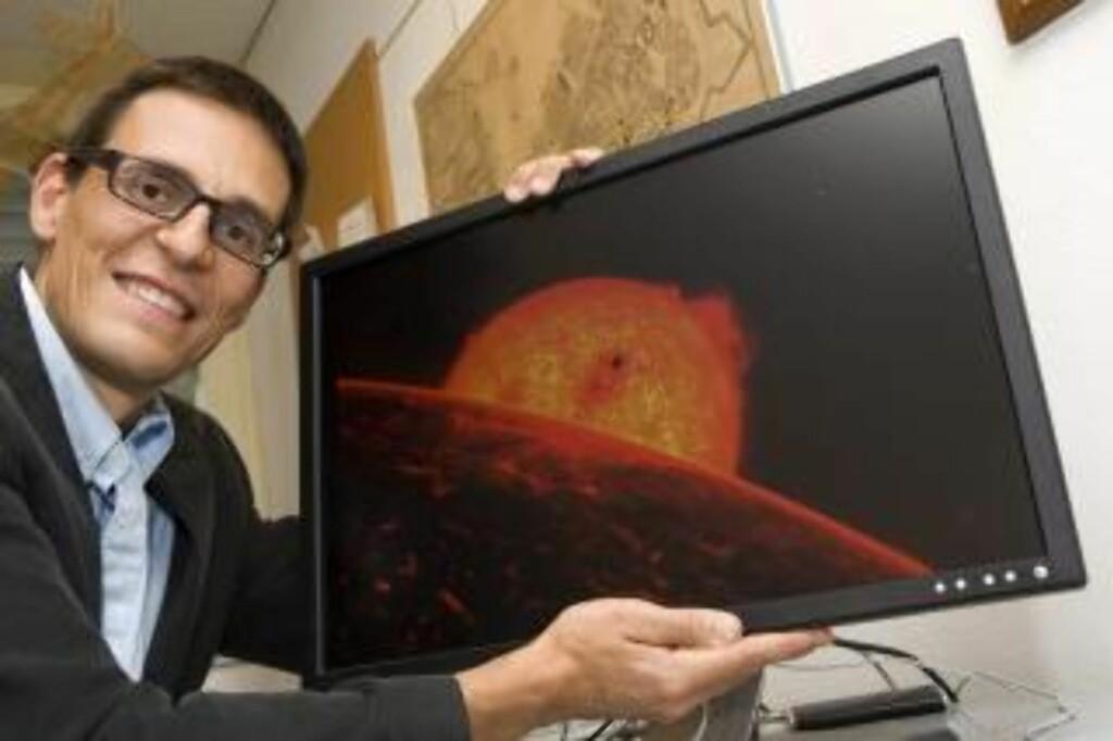 FORNØYD:  Den sveitsiske astronomen Didier Queloz poserer med en illustrasjon av Corot-7b, som han bidro til å avdekke. Foto: EPA/SALVATORE DI NOLFI