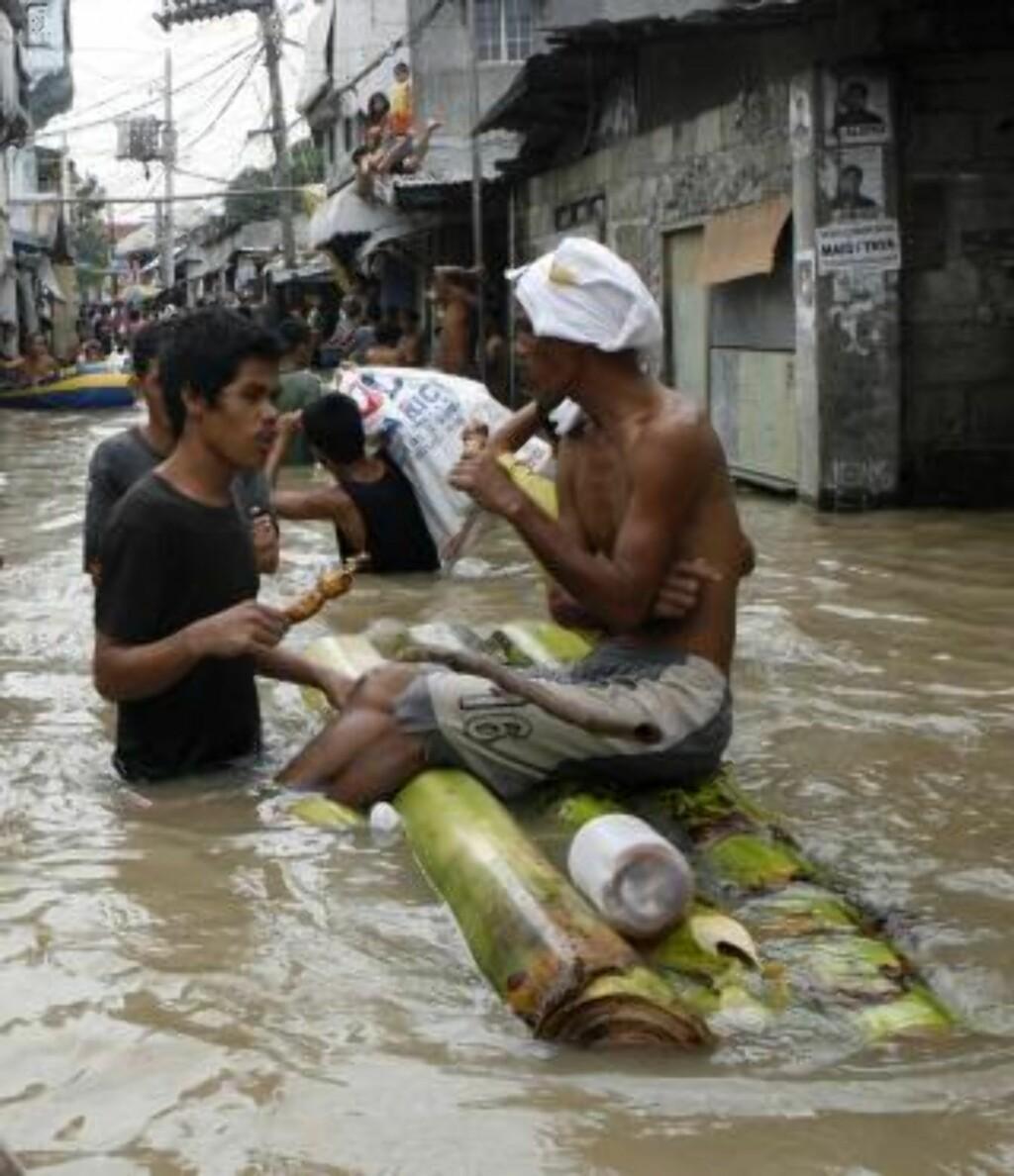 VANN OVERALT: To menn prøver å få i seg litt mat mens flomvannet står høyt i gatene i Binan Laguna, sør for Manila. Foto: REUTERS/Erik de Castro