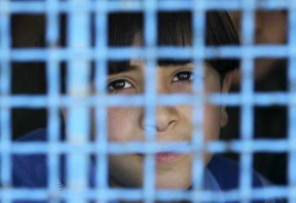 VERDENS STØRSTE UTENDØRS FENGSEL:  En palestinsk gutt ser ut av vinduet til FNs Faqora-skole, som ble bombet under krigen. FN kom nylig med en rapport der de mente at Israel ikke tok nok hensyn til FNs bygninger under det massive angrepet i desember-januar. Foto: Mohammed Salem/Reuters/Scanpix