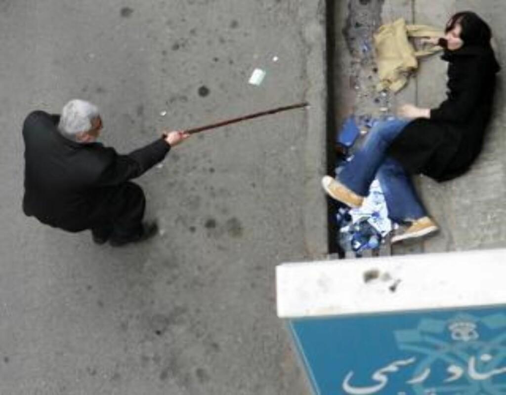 BLIR FORBUDT: Bilder som dette, som viser en mann som truer en kvinne med stokk, skal ikke lenger kunne tas. Iranske myndigheter kaster utenlandske reportere på dør. Foto:  REUTERS/Stringer/Scanpix