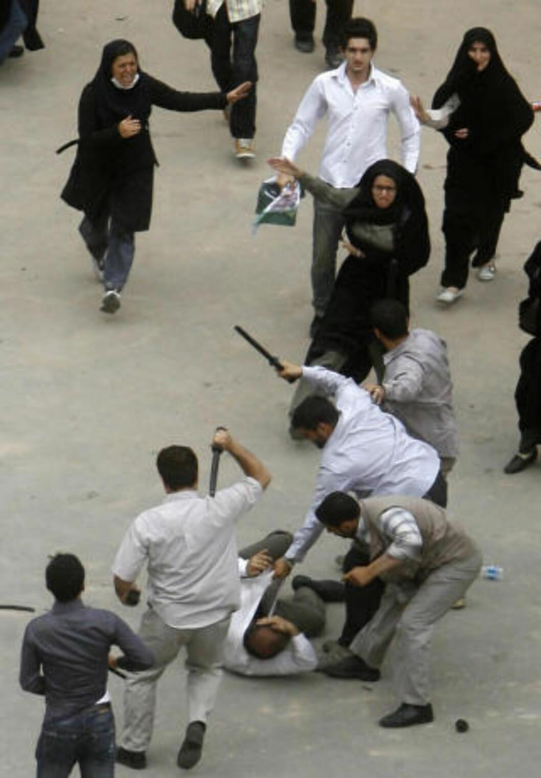 <strong>FRA DEMONSTRASJONENE:</strong> Iranske politimenn i sivilt angrekk slår en Mousavi-tilhenger med batonger i Teheran 14. juni i år. Foto: TOPSHOTS/AFP PHOTO/STR