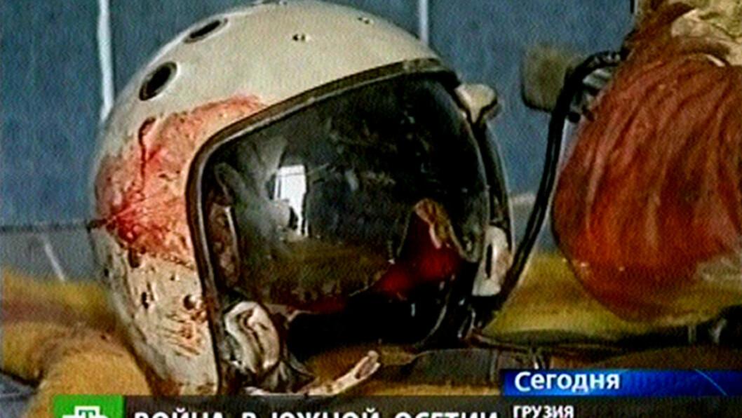 SKUTT NED AV SINE EGNE: En blodig pilothjelm ligger ved siden av båren til det som angivelig var en nedskutt russisk pilot. TV-bildene ble publisert av georgiske myndigheter 9. august i fjor, midt under den ti dager lange krigen med Russland. Foto: AP/NTV Russian Channel
