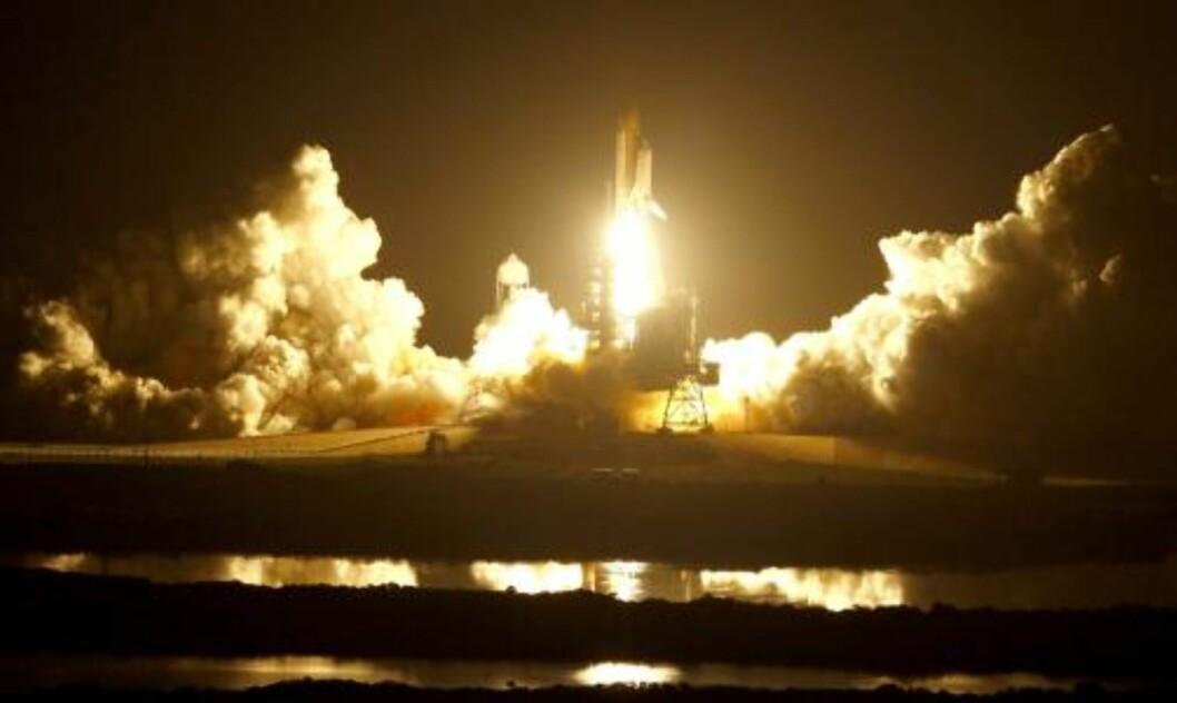 <strong>SPEKTAKULÆRT SYN:</strong> Kennedy Space Center badet i et oransje lys da rakettene på sidene av Discoverys drivstofftank ble antent. Foto: SCANPIX/EPA/Justin Dernier