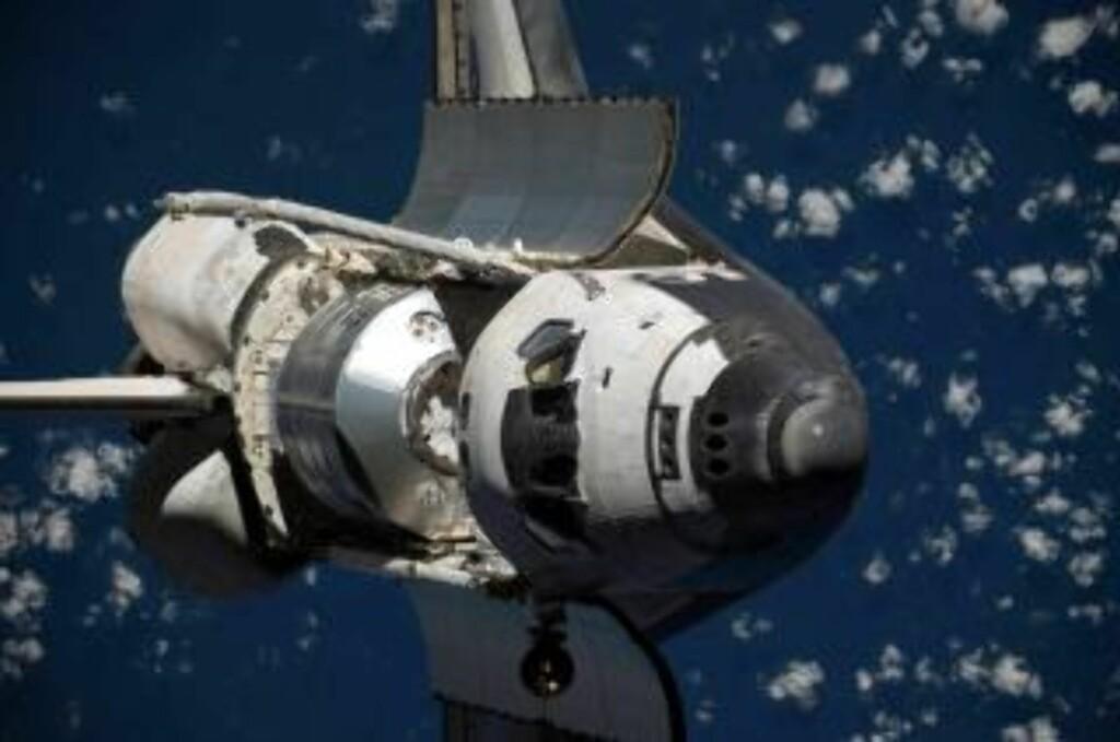PÅ EN SNURR: Discovery under den såkalte rendezvous pitch maneuver-en utenfor ISS. Romferja snurret 360 grader rundt slik at ISS-astronauter kunne fotografere skroget på jakt etter skader. Foto: Scanpix/EPA/NASA