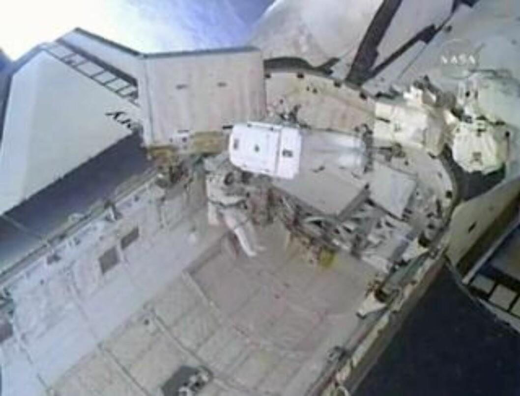 SNART FERDIG... Her er de i ferd med å føre den tomme tanken ned i Discoverys lasterom. Foto: REUTERS/NASA TV