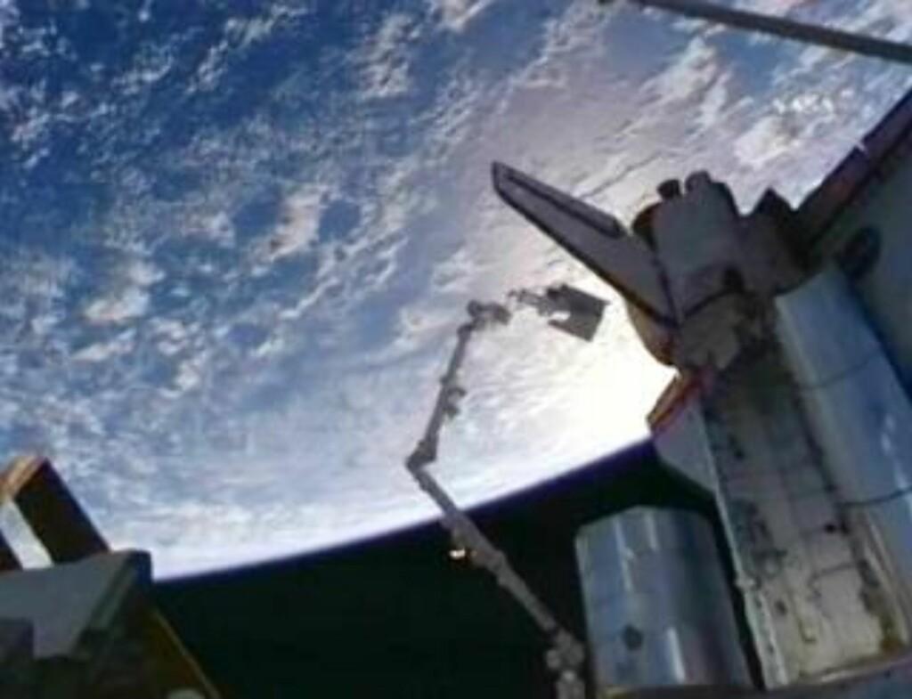 HØYT OPPE: Christer Fuglesang henger i enden av en robotarm som assisterte ham i skiftet av en tom ammoniakktank på ISS. Foto: NASA TV