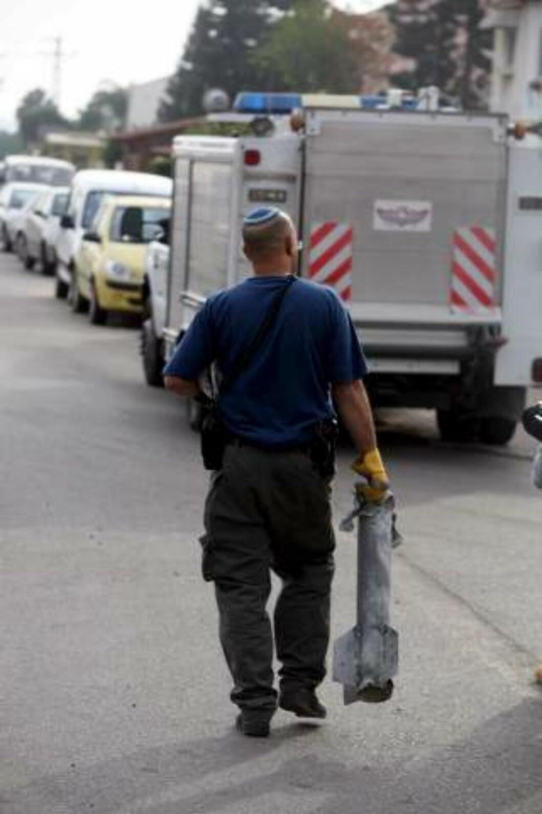<strong>RAKETTEN:</strong> En israelsk politimann bærer en Qassam-rakett som  i dag traff et hus i Sderot. EPA/PAVEL WOLBERG