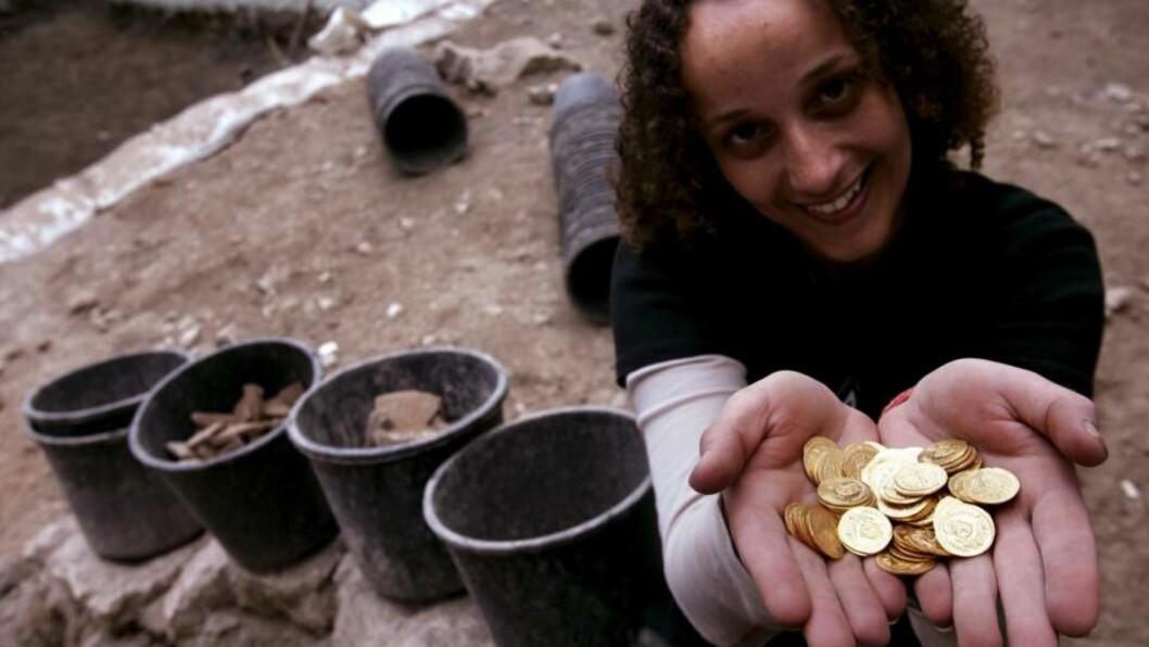 <strong>VISER FRAM:</strong> En arbeider viser her stolt frem noen av gullmyntene som nylig ble funnet i Jerusalem. Foto: OLIVIER FITOUSSI/SCANPIX