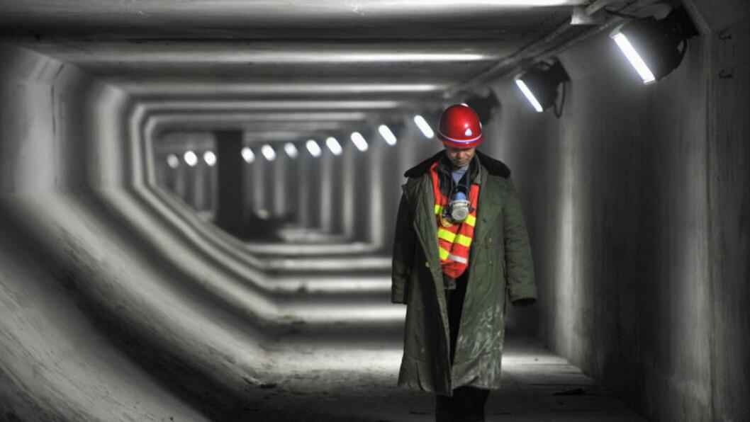 <strong>FERDIG:</strong> En arbeider rusler gjennom servicedelen av den nye tunnelen. Foto: REUTERS/China Daily
