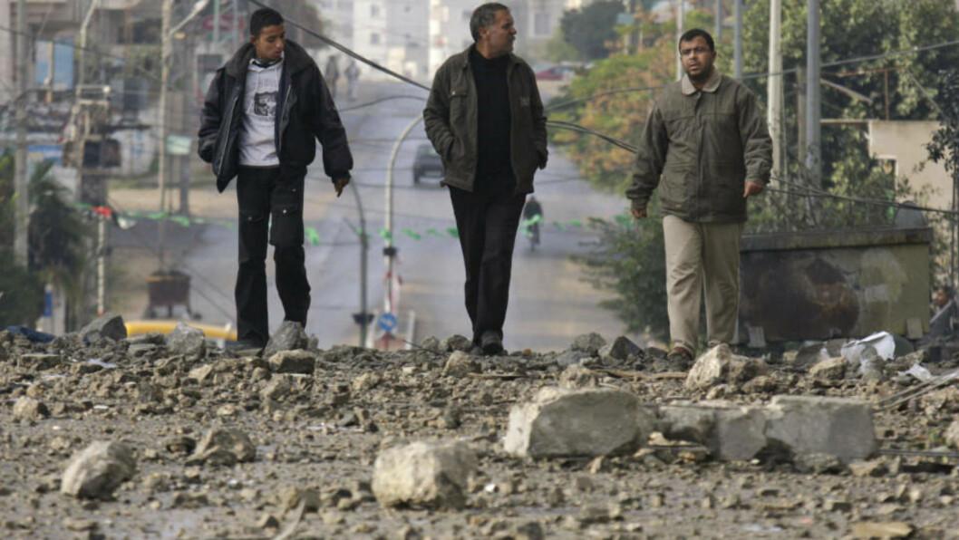 <strong>FORTSETTER ANGREP:</strong> Tirsdag kveld fortsetter angrepene mot Gazastripen. Her går tre menn i gatene i Gaza by tirsdag. Foto: AP/SCANPIX