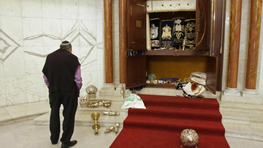 <strong>VANDALISERT:</strong>  Et medlem av det jødiske samfunnet ser på det vandalisterte alteret i en synagoge i Caracas i Venezuela. Nå er 11 personer pågrepet for angrepet. Foto: AP Photo/Carlos Hernandez