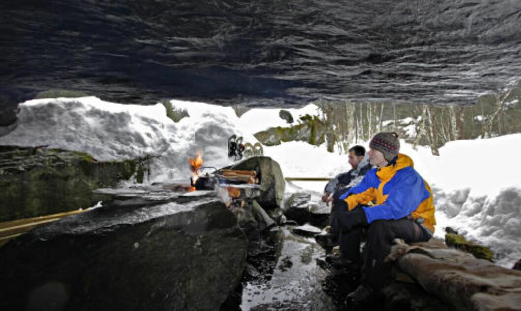 <strong>GROTTE:</strong> Under en kampestein er det en naturlig grotte hvor det er bålplass og sittebenk. José Ravelo og Frode Solbakk venter på varmen fra bålet.