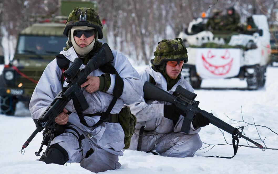 <strong>KALDT:</strong> To danske soldater forsøker å holde varmen under Cold Response i indre Troms. Begge har på seg norske feltskjorter, vinterkamuflasje og ullundertøy. Foto: Erik Drabløs/Forsvaret