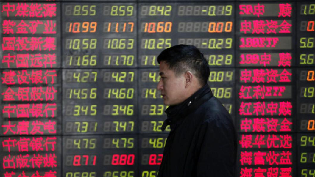 <strong>DYSTRE UTSIKTER:</strong> En investor passerer en oversikt over aksjekurser i Shanghai i Kina. Foto: Eugene Hoshiko/AP