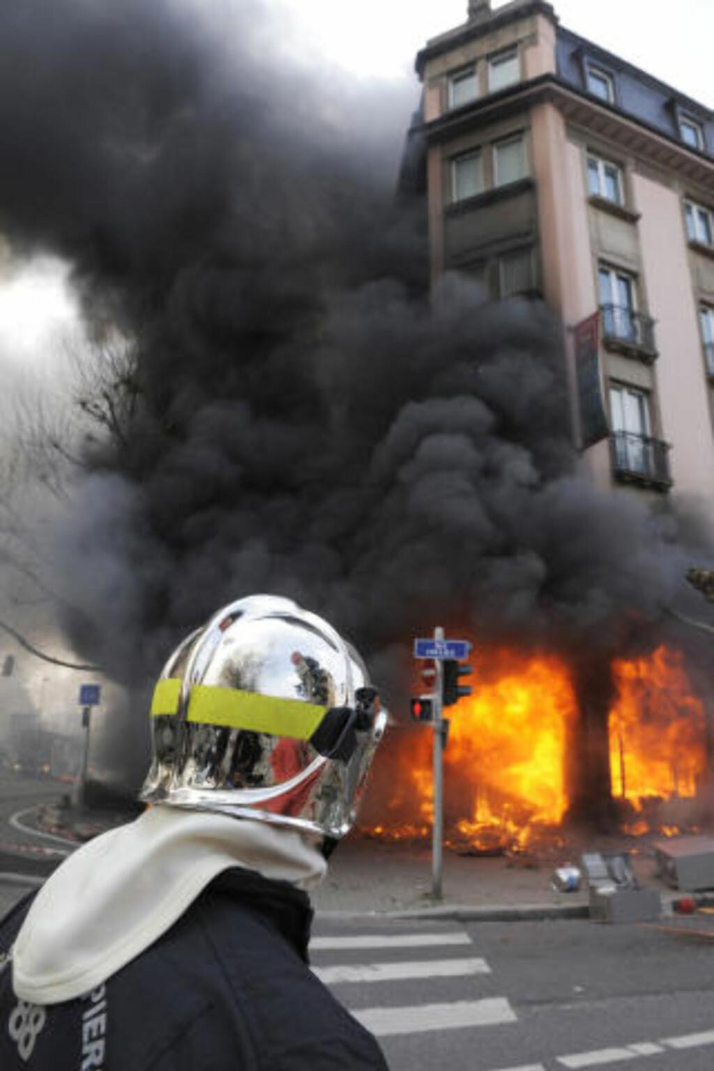 BRENNER NED: Protestene ble opptøyer rundt klokken 12 i dag.  Foto: AFP PHOTO DDP / AXEL SCHMIDT