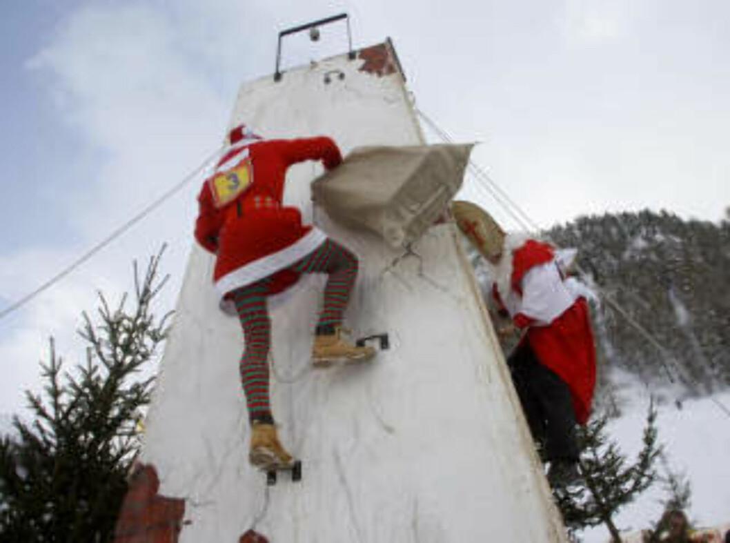 <strong>PIPEKLATRING:</strong> Alle nisser som kjemper om å bli verdens beste, må klatre den fem meter høye pipa. Dette er én av utfordringene under årets Clau Wau, kampen om å bli verdens beste nisse, i Samnaun i Sveits. Foto: REUTERS/Arnd Wiegmann/SCANPIX