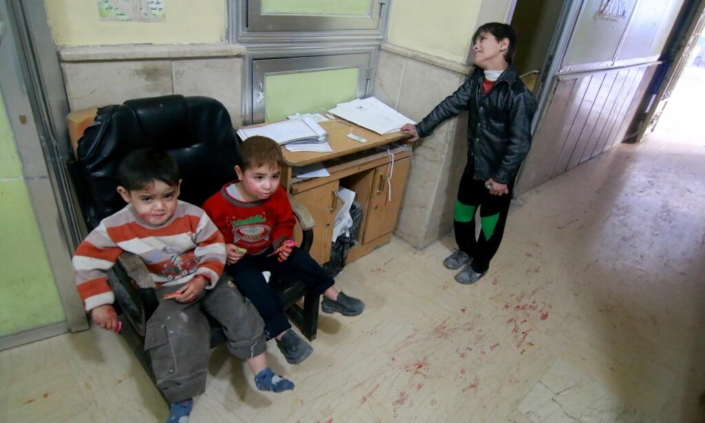 FORLATT AV VERDEN. Disse barna ble alle skadd i voldsomme bombeangrep i den syriske byen Aleppo i går, og sitter og venter på medisinsk behandling på Sahra-sykehuset. Syriske og russiske fly angrep den opposisjonskontrollerte byen i går. Minst 94 personer skal være drept og mer enn 150 ble skadd. Foto: Jawad al Rifai / Anadolu Agency / Scanpix
