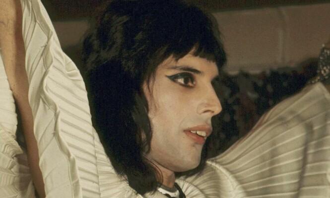 LEKTE MED KJØNNSROLLER: Allerede tidlig inn i Queen og Freddie Mercurys karriere, her i 1974, gikk vokalisten i bresjen for andre kjønnsutrykk og utfordret dermed folk oppfatning av maskulinitet. Her i en kreasjon fra Zandra Rhodes. Foto: Rex Features, NTB scanpix