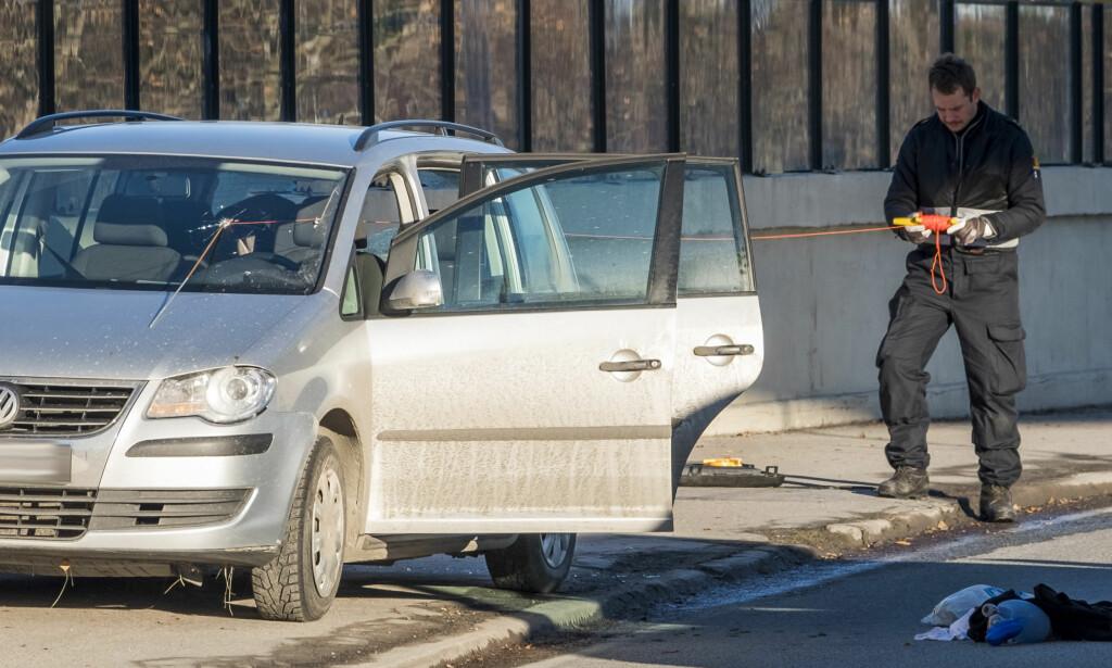 Drept: En mann ble skutt og drept  av politiet natt til søndag. Bildet viser kulehull i frontruta på bilen avdøde kjørte.  Politiets teknikere jobber med bilen. Foto: Tor Erik Schrøder / NTB scanpix