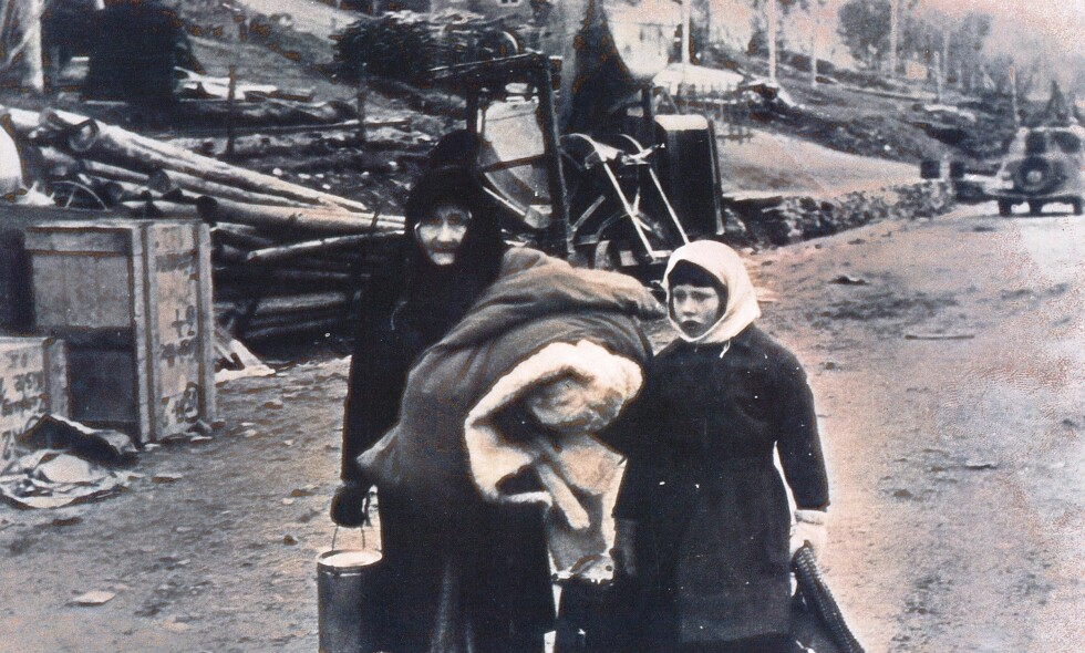 IKONISK BILDE: Hvem var kvinnen og den lille jenta - som den 6.november 1944 ble fotografert på kaia i Indre Billefjord? Forfatteren Roger Albrigtsen fant svaret. Det var Anna Malene Larsen og barnebarnet Petra Antona Henningsel på vei ombord i lastebåten som skulle ta dem sørover. Foto: Fra boka «Krigens vitner»
