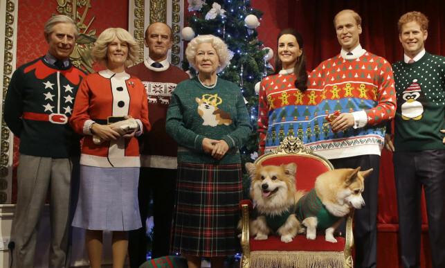 FAMILIEBILDE: Hele den britiske kongefamiliens voksdukker har fått nye antrekk til jul. Fra venstre ser vi prins Charles, hertuginne Camilla, prins Philip, dronning Elizabeth II, hertuginne Kate, prins William og prins Harry. For anledningen har museet også kledd opp flere corgi-hunder, dronningens favoritt. Foto: NTB scanpix