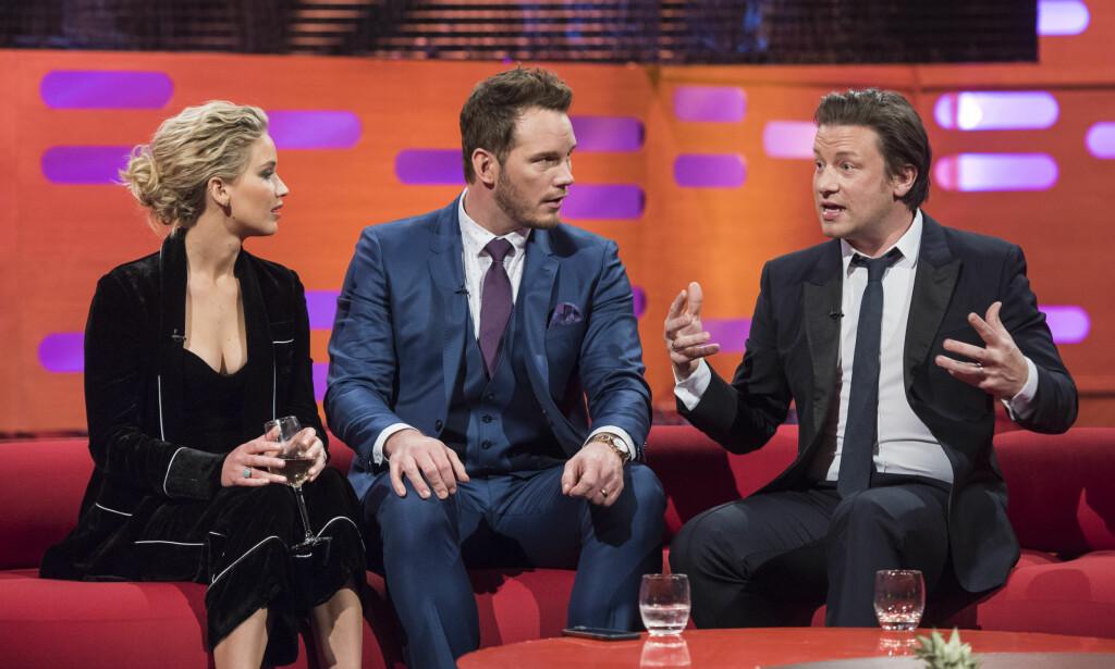 SUKSESSRIK: Tv-kokken Jamie Oliver (t.h.) har siden starten av 2000-tallet vært en kjent profil i en rekke land. Nå forteller han at tv-serien fikk blandet mottakelse hos den britiske befolkningen da den først ble lansert. Her gjester han «The Graham Norton Show» sammen med Jennifer Lawrence og Chris Pratt. Foto: NTB Scanpix