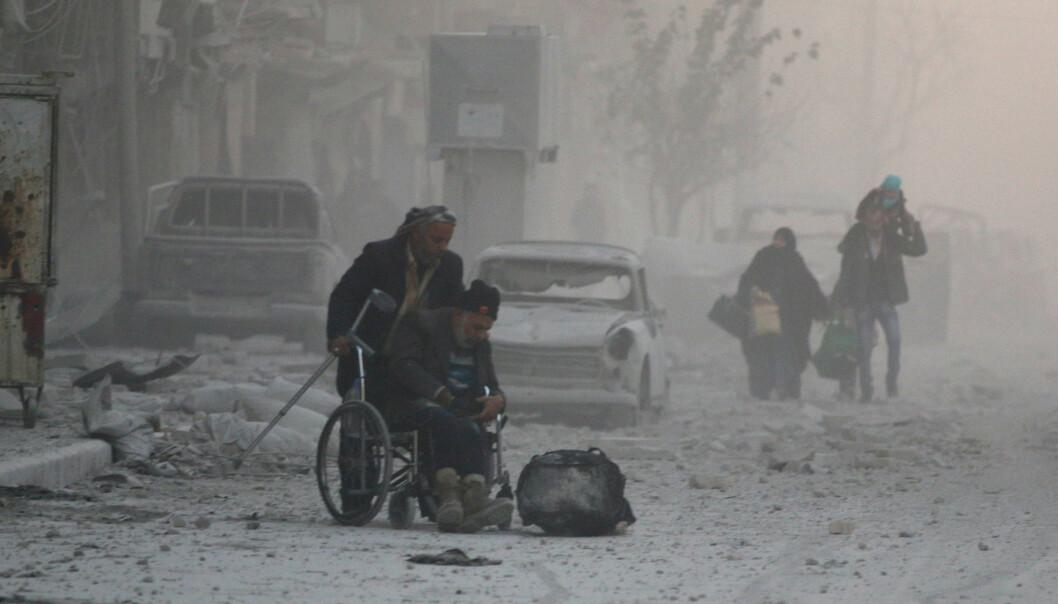 PÅ FLUKT: Den siste uka har titusener av mennesker flyktet fra Øst-Aleppo og til den vestlige delen av byen. Her hjelpes en mann i rullestol ut fra det som inntil for kort tid siden var kontrollert av opprørerne. Nå har Assads styrker tatt over. Foto: Abdalrhman Ismail / Reuters / Scanpix