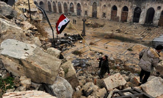 TRIUMFERER: En militssoldat lojal mot Syrias regjering reiser landets flagg i Umayyad-moskeen i Øst-Aleppo i dag. Foto: Omar Sanadiki / Reuters / NTB Scanpix