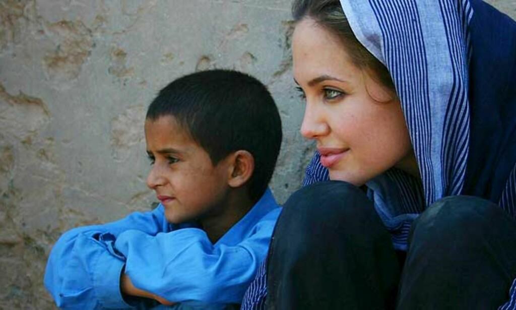 FN-ambassadør Angelina Jolie: Ved siden av en afghansk gutt i en flykningeleir nær Peshawar i Pakistan. Foto: Scanpix