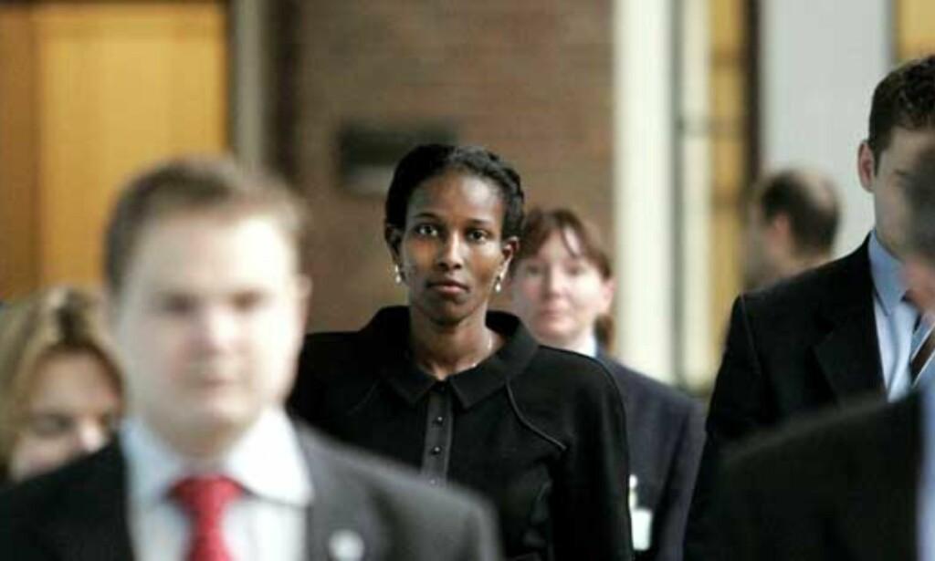 LEVER I FRYKT: Mange nederlendere ser dødstruslene mot Ayaan Hirsi Ali som et uutholdelig angrep på landets demokratiske prinsipper og ytringsfriheten. Men fortsatt må hun beskyttes døgnet rundt. Som her på vei inn i det nederlandske parlamentet, omgitt av livvakter. Foto: Scanpix