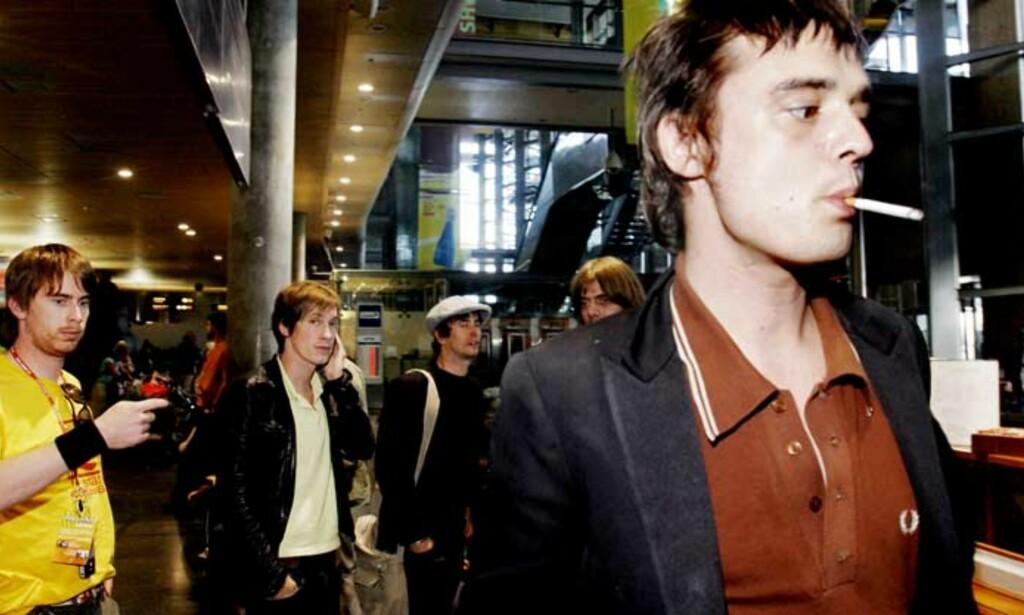LIKE BLID Den skandaleomsuste vokalisten i Babyshambles, Pete Doherty, smilte da han kom ut etter å ha sittet fast i tollkontrollen i tre timer. Bak t.v. en representant fra Øyafestivalen, bandets tour-manager og trommeslager Adam Ficek.