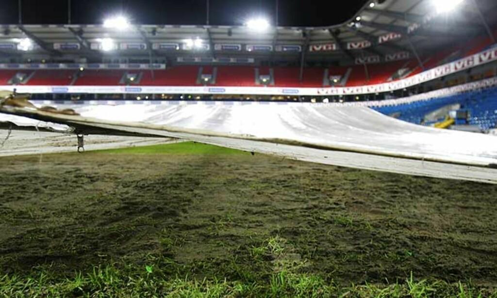 SPESIALTELT: Gressteppet på vår største fotballstadion er i dårlig stand etter mye regn og slitasje, og mannskaper jobber hardt for å få banen klar til kamp. Foto: SCANPIX