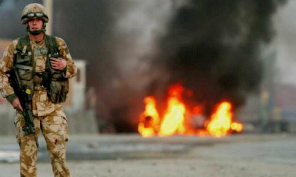 PRESSET: En britisk soldat står vakt foran det brennende vraket av et NATO-kjøretøy. Foto: Scanpix