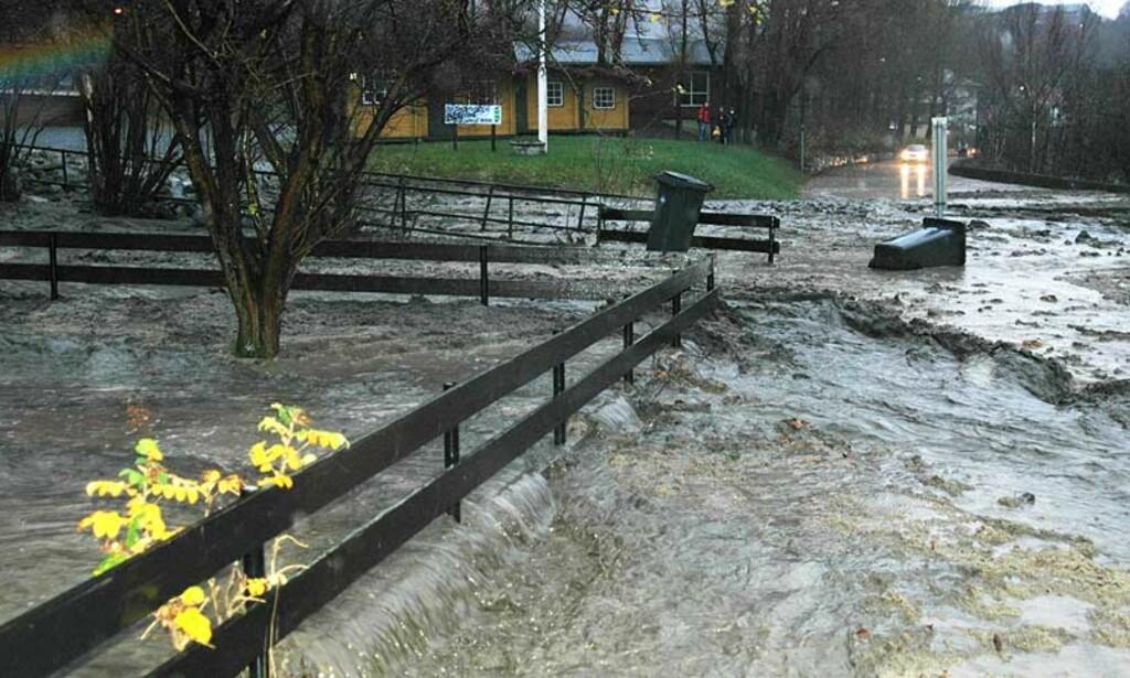 MER ENN 20 RAS I OMRÅDET: Her flommer vann, jord, og leire gjennom en hage og ut på en lokal vei på Årdalstangen i formiddag. Foto: Hanne Stedje/ Porten.no