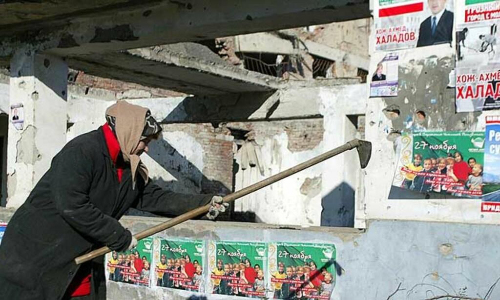 KRIGSHERJET: En kvinne arbeider ved et istykkerskutt hus, overklistret med valgpropaganda. Foto: Reuters/Scanpix