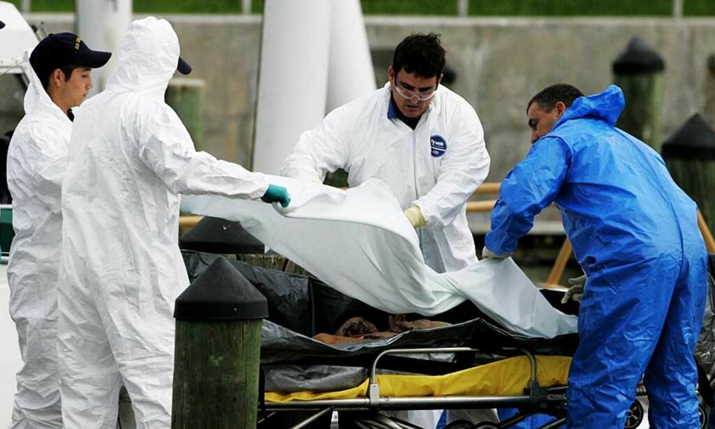 OMKOMMET: Redningsmannskaper dekker til en av de omkomne etter flyulykken utenfor Miami Beach. Foto: Scanpix