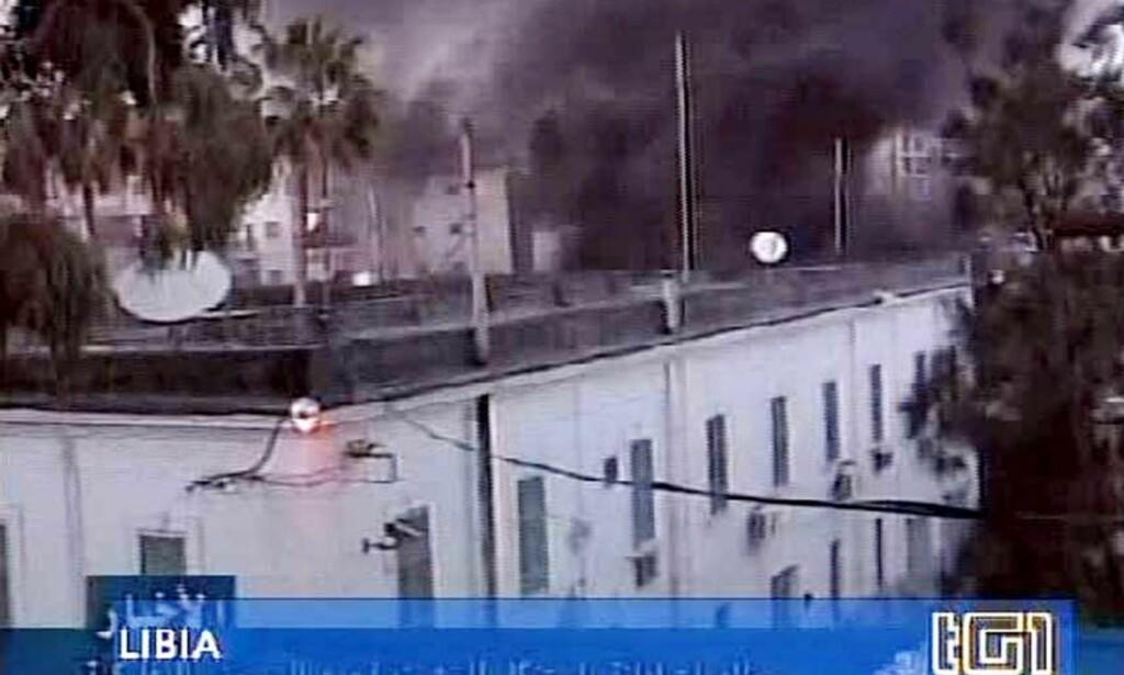 ANGREPET: Bildet fra den italienske fjernsynskanalen RAI viser sort røyk som stiger opp fra Italias konsulat i byen Beghazi i Libya. Rasende demonstranter gikk fredag kveld til angrep mot kosulatet i frustrasjon over den italienske reform-ministeren Roberto Calderolis Muhammed-utspill. 11 demonstranter ble drept og over 50 skadd i sammenstøtet med opprørspolitiet. Foto: RAI TG3