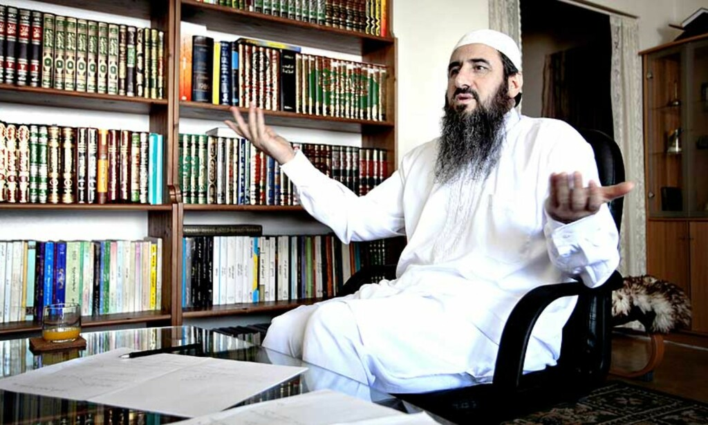 HJEMME HOS KREKAR:  Den ene veggen i stua er dekket med bøker. I et hjørne står datamaskinen som mulla Krekar bruker til å sende ut sine artikler og kommunisere med trosfeller over hele verden. -  Målet er islamsk makt i en islamsk stat, sier Krekar. Foto: Bjørn Langsem
