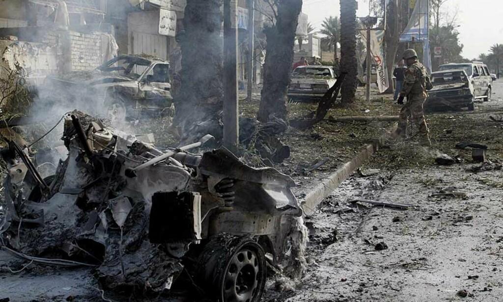 NOK EN BILBOMBE: Irakiske styrker på åstedet etter at en bilbombe eksploderte i det den britisk konvoy kom kjørende i Harithyahi-området i Bagdad i dag. Nå ønsker britene å trekke ut ti prosent av styrkene de har i Irak. Foto: MOHAMMED JALIL/EPA