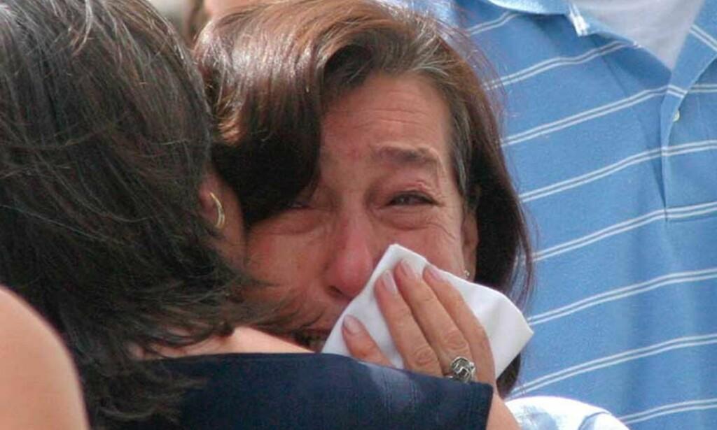 SØRGER: Moren til en av de ti savnede får støtte. Hun frykter sønnen er omkommet i flommen. Foto: AP